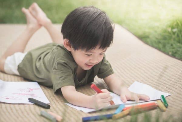 child drawing picture with crayon