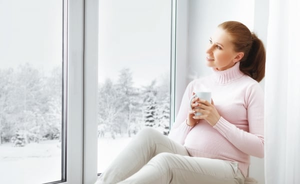 Happy young pregnant woman with  cup of tea on  window