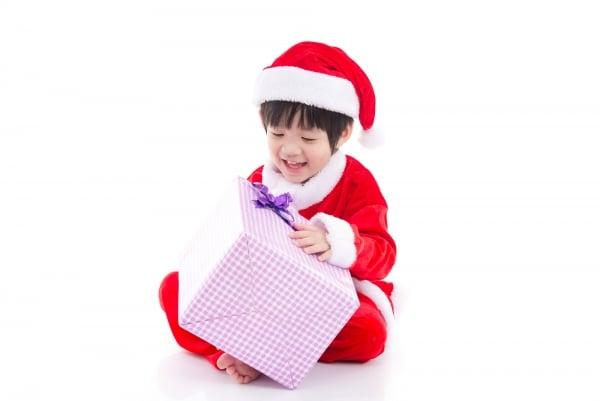 sian boy in santa claus uniform holding big gift box
