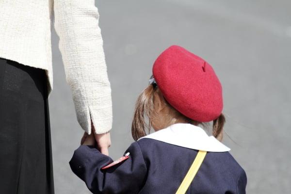 お母さんと手を握る幼稚園の制服の幼児(3歳児) (後姿)