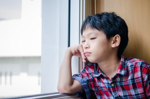 Sad Asian boy looking out of window