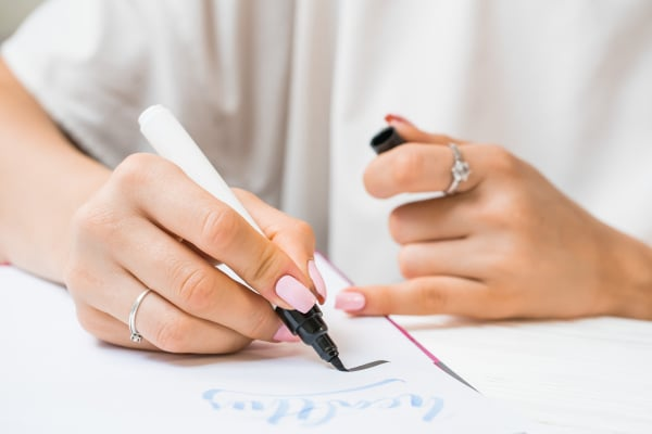 Calligrapher student practices in writing word inspire with green marker on canvas. Creative artist freelancer working on project at home studio. Lettering, handwriting concept.