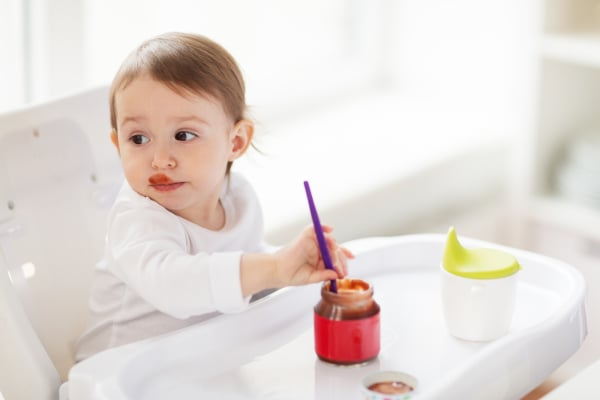 baby with spoon eating puree from jar at home