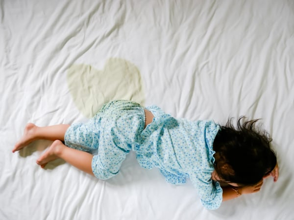 Child pee on a mattress, Little girl feet and pee in bed sheet, Child development concept , selected focus