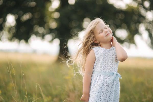 Little girl in sky blue dress stand in field in front of big tree