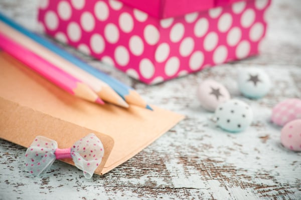 Empty envelope with blue and pink pencils