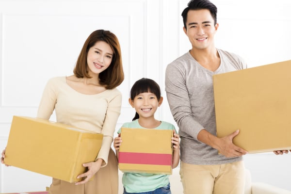 happy family holding box moving to new home