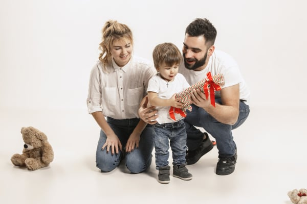 happy family with kid sitting together and smiling at camera isolated on white