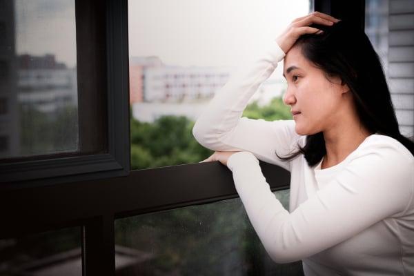 depressed women sitting near window, alone, sadness, emotional c