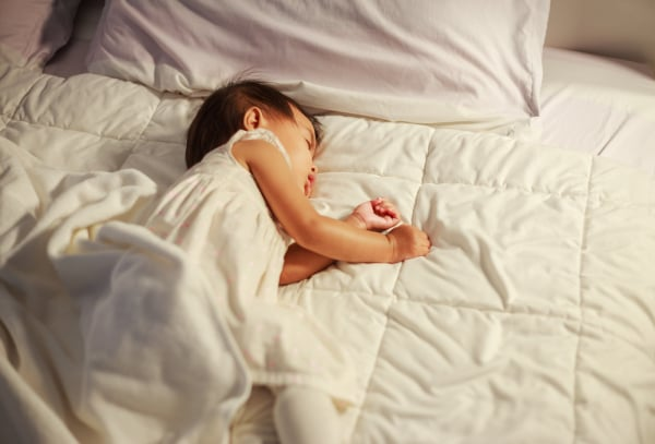 baby sleeping on bed at home
