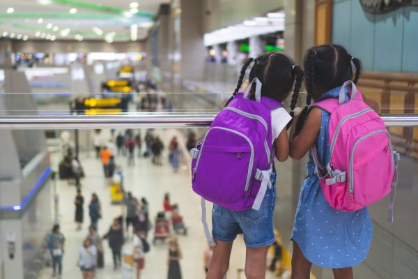 Two cute asian child girls with backpack waiting for boarding in