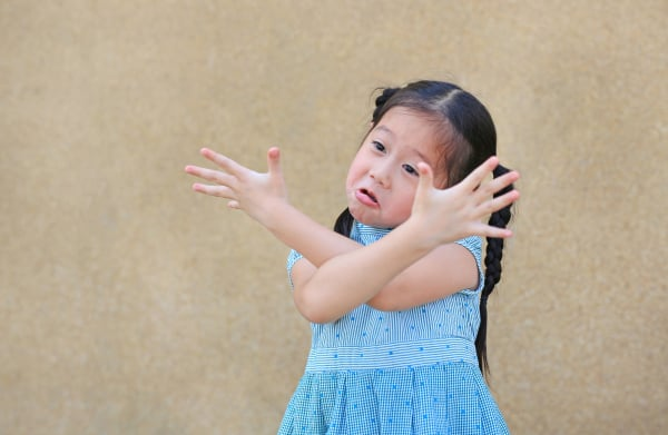 Sassy little Asian kid girl with funny face and expression cross one's arm.