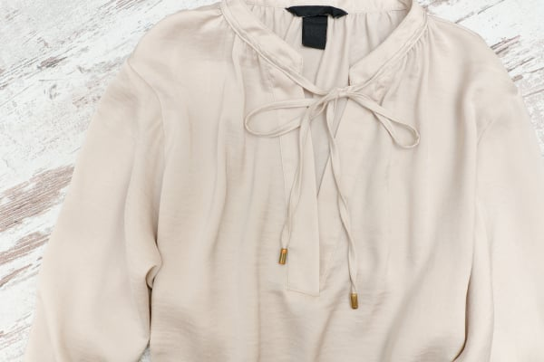 Beige blouse on a wooden background. Fashionable concept