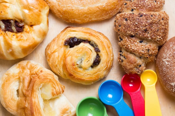 Mixed variety of fresh bakery products on wood plate background