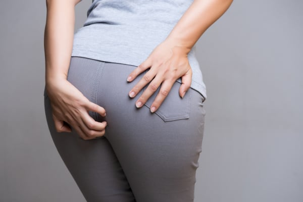 Woman suffering from hemorrhoids and hand holding her bottom bec