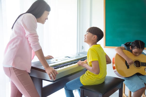 Beautiful asian female teacher teaching kids playing Music Instr