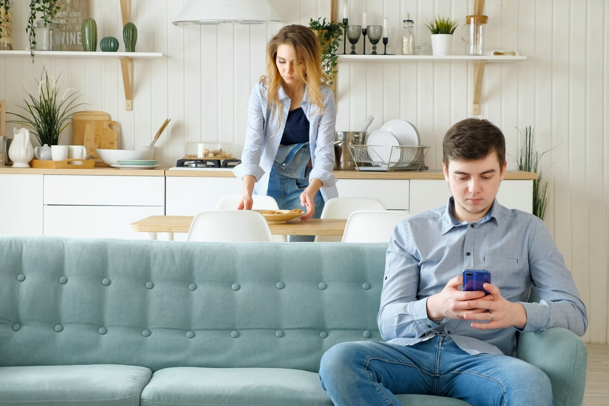 wife takes away dishes husband sits on sofa with phone