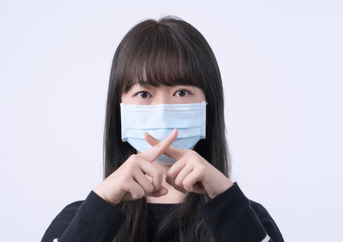 Portrait of young Asian woman, saying no to coronavirus infection with wearing medical surgical blue face mask isolated on white background, close up, closeup.