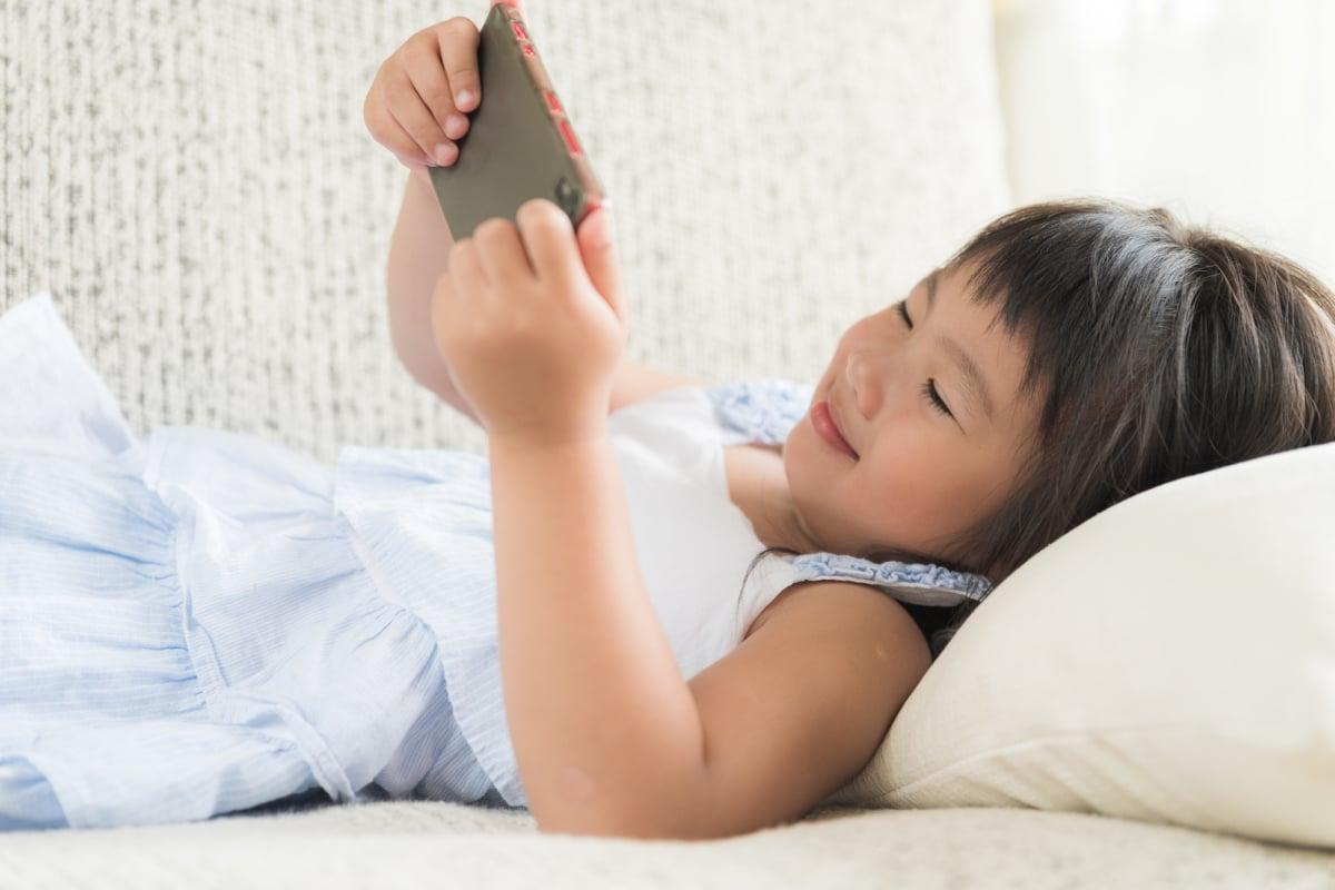 Cute little girl having fun to play game on smart phone lying on