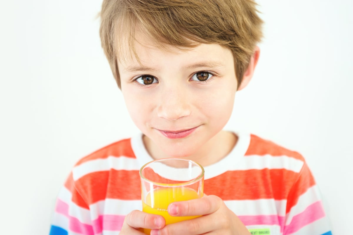 Portrait of a young boy who is drinking juice in the white background.