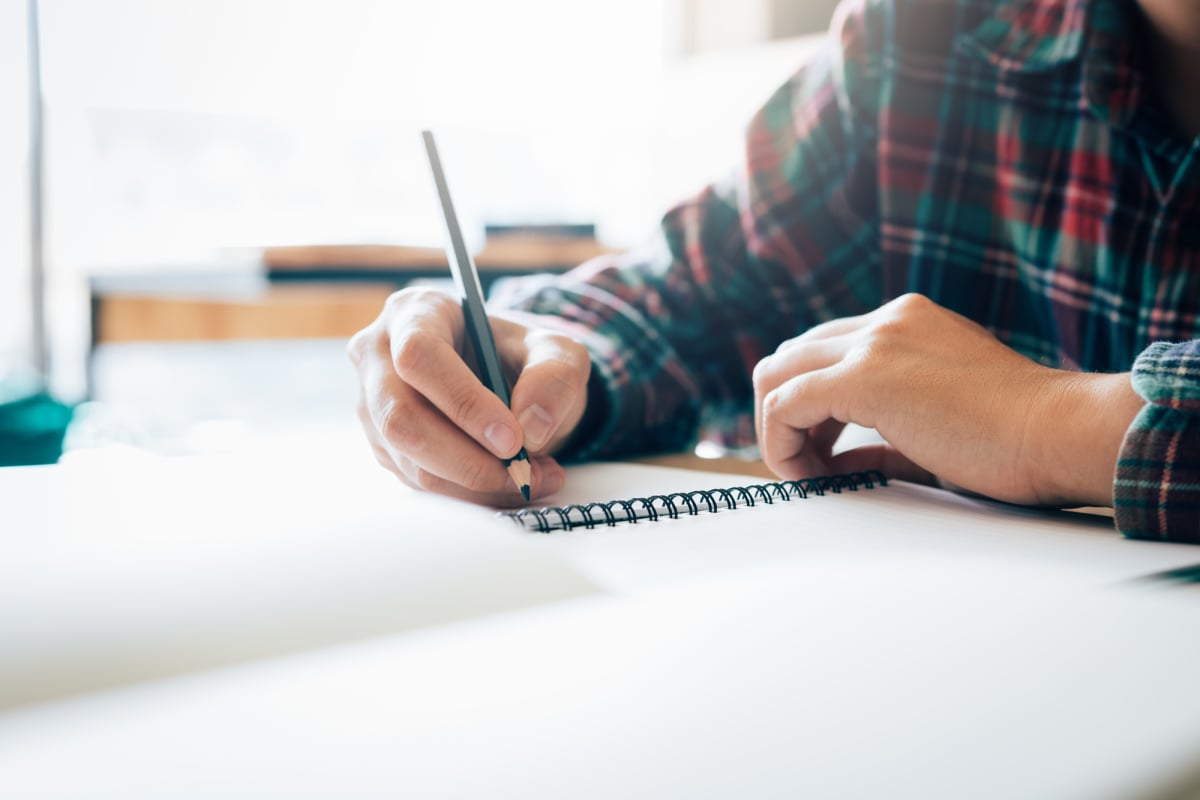 Teenage student works on homework in his room and writing in not