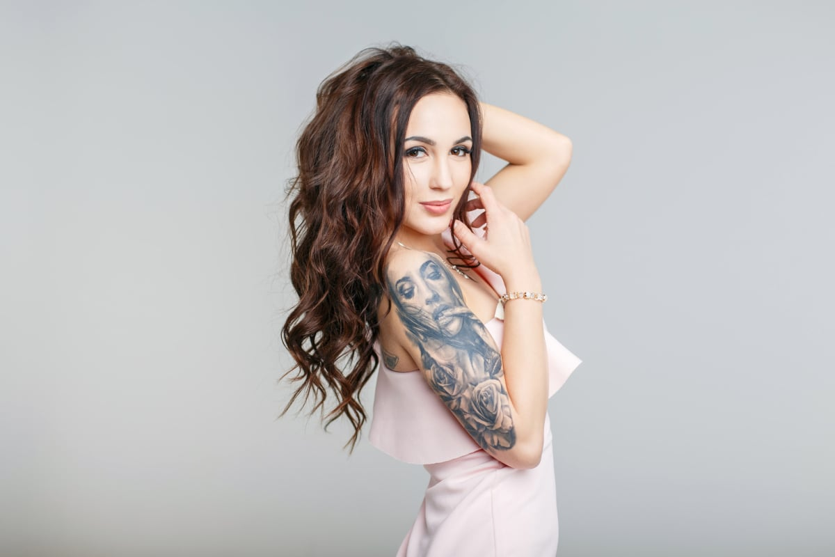 Beautiful young woman with stylish tattoo on hand in pink dress
