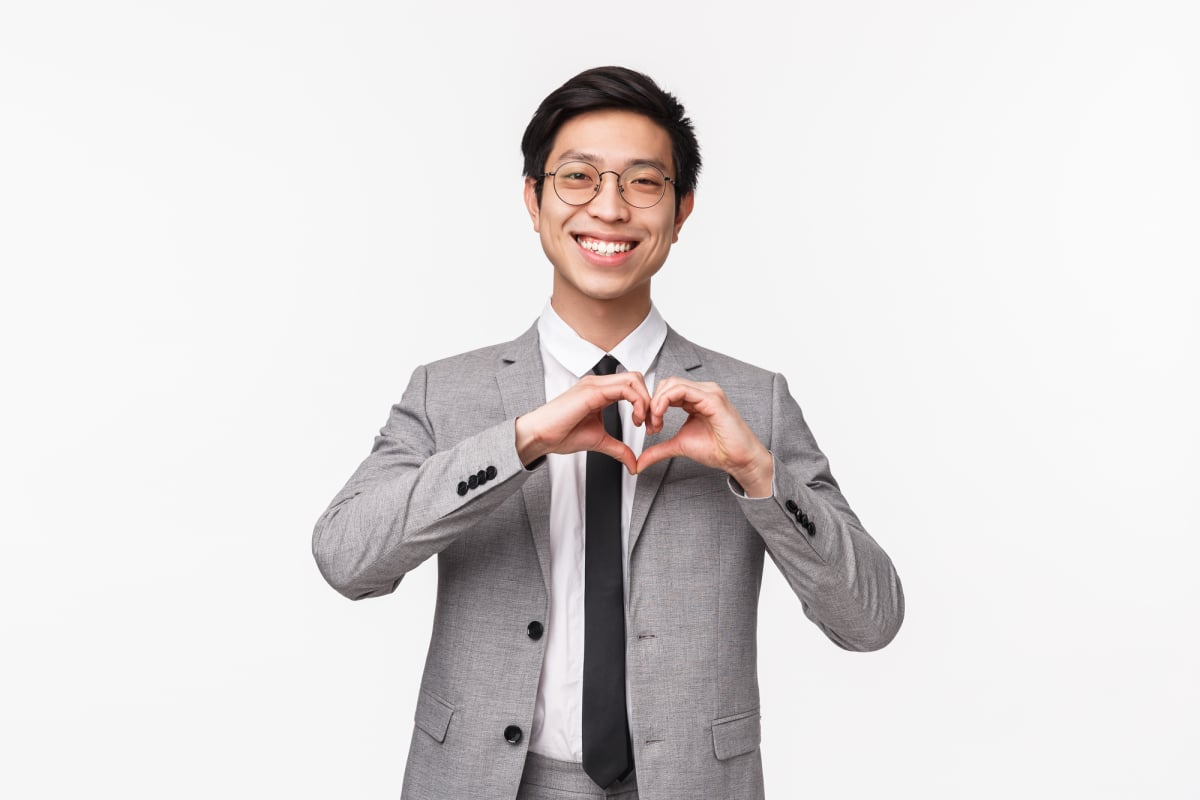 Waist-up portrait of lovely, cute asian young man, office manager in suit, showing heart sign and smiling blushing, expressing his sympathy, confessing in love, standing white background