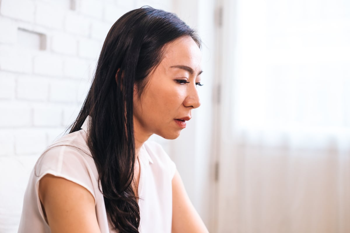 Sad thoughtful Asian female at home