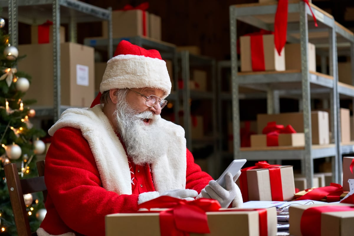 Happy Santa Claus holding cell phone using mobile app sitting at workshop table.