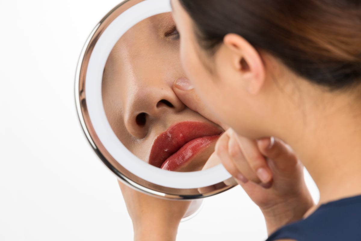 鏡で鼻を見る女性
