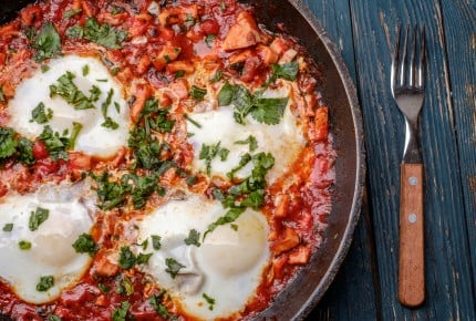 Fried eggs in a frying pan with tomatoes, sausage and greens