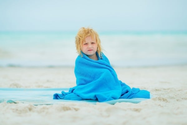 Baby girl wrapped in towel sitting on beach
